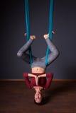 Νέα όμορφη γυναίκα brunette που κάνει τη γιόγκα μυγών Κάθισμα στο hammoc Στοκ εικόνα με δικαίωμα ελεύθερης χρήσης