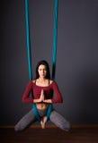 Νέα όμορφη γυναίκα brunette που κάνει τη γιόγκα μυγών Κάθισμα στο hammoc Στοκ Εικόνες