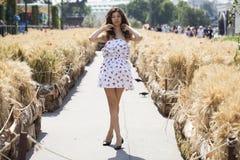 Νέα όμορφη γυναίκα brunette στο άσπρο φόρεμα που περπατά στο στρεπτόκοκκο Στοκ εικόνες με δικαίωμα ελεύθερης χρήσης