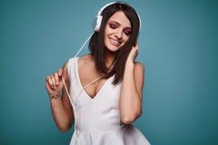 Νέα όμορφη γυναίκα brunette στο φόρεμα με τα ακουστικά στοκ φωτογραφίες