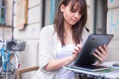 Νέα όμορφη εκμετάλλευση Ipad γυναικών που κοιτάζει μακριά. Στοκ φωτογραφία με δικαίωμα ελεύθερης χρήσης
