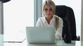 Νέα όμορφη επιχειρηματίας που εργάζεται στον υπολογιστή στο γραφείο της απόθεμα βίντεο