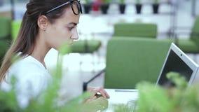 Νέα όμορφη επιχειρηματίας που εργάζεται στο lap-top στο φωτεινό σύγχρονο γραφείο φιλμ μικρού μήκους