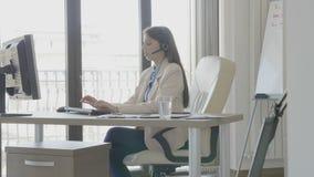 Νέα όμορφη επιχειρηματίας που μιλά στην κάσκα στο γραφείο απόθεμα βίντεο