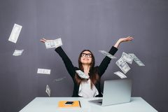 Νέα όμορφη επιχειρηματίας που ρίχνει επάνω στα χρήματα, που κάθονται στη θέση γραφείων με το lap-top στοκ φωτογραφίες