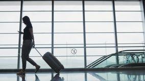 Νέα όμορφη επιχειρηματίας που χρησιμοποιεί ένα Smartphone στον αερολιμένα περιμένοντας τη σειρά αναμονής της την εγγραφή, που ταξ Στοκ Φωτογραφίες