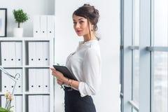 Νέα όμορφη επιχειρηματίας που χρησιμοποιεί την ταμπλέτα με Διαδίκτυο στην αρχή, τα μηνύματα ανάγνωσης και αποστολής, χαμόγελο, πο στοκ φωτογραφία με δικαίωμα ελεύθερης χρήσης