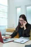 Νέα όμορφη επιχειρησιακή γυναίκα με το σημειωματάριο στο γραφείο Στοκ Εικόνες