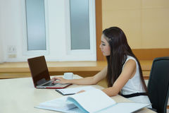 Νέα όμορφη επιχειρησιακή γυναίκα με το σημειωματάριο στο γραφείο Στοκ Εικόνα