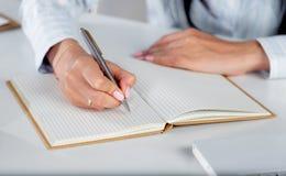 Νέα όμορφη επιχειρησιακή γυναίκα με το σημειωματάριο στο γραφείο Στοκ εικόνα με δικαίωμα ελεύθερης χρήσης