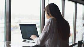 νέα όμορφη επιχειρησιακή γυναίκα στο άσπρο πουκάμισο που λειτουργεί στο γραφείο με το lap-top και το έγγραφο στον καφέ φιλμ μικρού μήκους