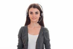 Νέα όμορφη επιχειρησιακή κυρία με το ακουστικό και το μικρόφωνο που εξετάζουν τη κάμερα και χαμόγελο που απομονώνεται στο λευκό Στοκ Εικόνες