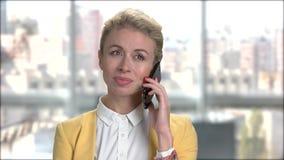 Νέα όμορφη επιχειρησιακή κυρία που μιλά στο smartphone απόθεμα βίντεο