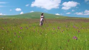 Νέα όμορφη ευτυχής γυναίκα που μένει στο μακρύ φόρεμα λιβαδιών που κυματίζει στον αέρα Όμορφο κορίτσι smilind στο στεφάνι λουλουδ απόθεμα βίντεο