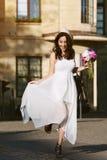 Νέα όμορφη ευτυχής χαμογελώντας κυρία που περπατά στην οδό, που κρατά το φλυτζάνι εγγράφου με τον καφέ Πρότυπα φορώντας μοντέρνα  Στοκ εικόνες με δικαίωμα ελεύθερης χρήσης