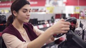 Νέα όμορφη θηλυκή επιλογή κοστουμιών που συναγωνίζεται weel για PS4 στο τμήμα ηλεκτρονικής στο κατάστημα συσκευών απόθεμα βίντεο