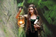 Νέα όμορφη θηλυκή νεράιδα που περπατά μέσω του δάσους με ένα boo Στοκ εικόνες με δικαίωμα ελεύθερης χρήσης