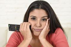 Νέα όμορφη ισπανική γυναίκα που προσέχει στο σπίτι την τηλεόραση που κουράζεται και που τρυπιέται Στοκ εικόνες με δικαίωμα ελεύθερης χρήσης