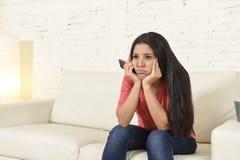 Νέα όμορφη ισπανική γυναίκα που προσέχει στο σπίτι την τηλεόραση που κουράζεται και που τρυπιέται Στοκ Φωτογραφίες