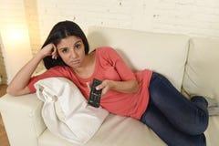Νέα όμορφη ισπανική γυναίκα που προσέχει στο σπίτι την τηλεόραση που κουράζεται και που τρυπιέται Στοκ φωτογραφία με δικαίωμα ελεύθερης χρήσης