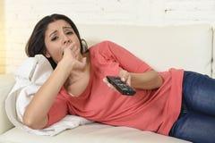 Νέα όμορφη ισπανική γυναίκα που προσέχει στο σπίτι την τηλεόραση που κουράζεται και που τρυπιέται Στοκ εικόνα με δικαίωμα ελεύθερης χρήσης