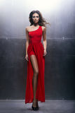 Νέα, όμορφη και εμπαθής γυναίκα σε ένα κυματιστό, μακρύ φόρεμα Στοκ Εικόνα