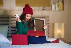 Νέα όμορφη και ευτυχής ασιατική αμερικανική πιστωτική κάρτα εκμετάλλευσης κρεβατιών γυναικών στο σπίτι και Χριστούγεννα αγορών κι στοκ εικόνα με δικαίωμα ελεύθερης χρήσης