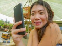 Νέα όμορφη και ευτυχής ασιατική κινεζική γυναίκα που χρησιμοποιεί τα κοινωνικά μέσα app Διαδικτύου στο κινητό τηλέφωνο που χαμογε Στοκ φωτογραφία με δικαίωμα ελεύθερης χρήσης