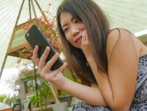 Νέα όμορφη και ευτυχής ασιατική κινεζική γυναίκα που χρησιμοποιεί τα κοινωνικά μέσα app Διαδικτύου στο κινητό τηλέφωνο που χαμογε Στοκ εικόνες με δικαίωμα ελεύθερης χρήσης