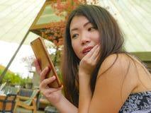 Νέα όμορφη και ευτυχής ασιατική κινεζική γυναίκα που χρησιμοποιεί τα κοινωνικά μέσα app Διαδικτύου στο κινητό τηλέφωνο που χαμογε Στοκ φωτογραφίες με δικαίωμα ελεύθερης χρήσης