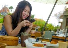 Νέα όμορφη και ευτυχής ασιατική κινεζική γυναίκα που χρησιμοποιεί τα κοινωνικά μέσα app Διαδικτύου στο κινητό τηλέφωνο που χαμογε Στοκ Εικόνες