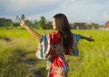 Νέα όμορφη και ευτυχής ασιατική κινεζική γυναίκα τουριστών στη δεκαετία του '20 της με το ζωηρόχρωμο φόρεμα που παίρνει selfie το Στοκ Εικόνες