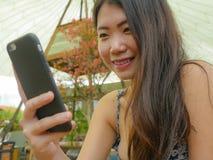 Νέα όμορφη και ευτυχής ασιατική κορεατική γυναίκα που χρησιμοποιεί τα κοινωνικά μέσα app Διαδικτύου στο κινητό τηλέφωνο που χαμογ Στοκ Εικόνες