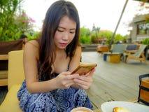 Νέα όμορφη και ευτυχής ασιατική κορεατική γυναίκα που χρησιμοποιεί τα κοινωνικά μέσα app Διαδικτύου στο κινητό τηλέφωνο που χαμογ Στοκ Εικόνα