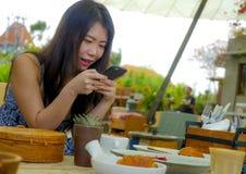 Νέα όμορφη και ευτυχής ασιατική κορεατική γυναίκα που χρησιμοποιεί τα κοινωνικά μέσα app Διαδικτύου στο κινητό τηλέφωνο που χαμογ Στοκ Φωτογραφία