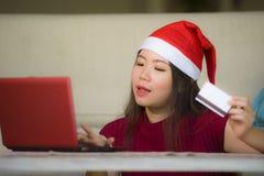Νέα όμορφη και ευτυχής ασιατική κορεατική γυναίκα στην πιστωτική κάρτα εκμετάλλευσης καπέλων Άγιου Βασίλη Χριστουγέννων που χρησι στοκ εικόνες