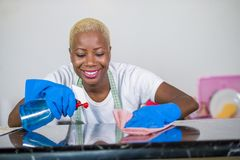 Νέα όμορφη και ευτυχής μαύρη γυναίκα αφροαμερικάνων στα λαστιχένια ενδύματα πλύσης που καθαρίζουν την εγχώρια κουζίνα με το χαμόγ στοκ φωτογραφίες με δικαίωμα ελεύθερης χρήσης