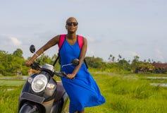 Νέα όμορφη και ευτυχής μαύρη γυναίκα αφροαμερικάνων τουριστών που εξετάζει γύρω με τη μοτοσικλέτα μηχανικών δίκυκλων τα πράσινα τ στοκ φωτογραφίες