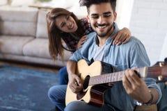Νέα όμορφη κιθάρα παιχνιδιού ατόμων για τη φίλη του στοκ φωτογραφία