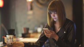 Νέα όμορφη κοκκινομάλλης συνεδρίαση γυναικών στον καφέ ή το φραγμό και χρησιμοποίηση ενός smartphone απόθεμα βίντεο