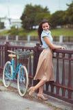 Νέα όμορφη, κομψά ντυμένη γυναίκα με το ποδήλατο Στοκ Φωτογραφίες