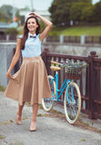 Νέα όμορφη, κομψά ντυμένη γυναίκα με το ποδήλατο Στοκ φωτογραφία με δικαίωμα ελεύθερης χρήσης