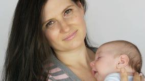 Νέα όμορφη μαύρος-μαλλιαρή μακρυμάλλης μητέρα με το δίμηνο νεογέννητο μωρό που ύπνοι στα όπλα της Λίκνα μαμών αυτή απόθεμα βίντεο