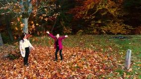 Νέα όμορφη μητέρα και η νέα κόρη της που έχουν τη διασκέδαση στο δάσος φθινοπώρου πηδούν και ρίχνουν τα φύλλα στον αέρα απόθεμα βίντεο
