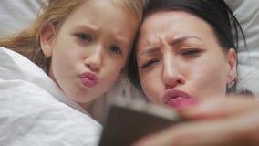 Νέα όμορφη μητέρα και η χαριτωμένη κόρη της που παίρνουν selfie με το smartphone και που χαμογελούν στο κρεβάτι στο σπίτι φιλμ μικρού μήκους