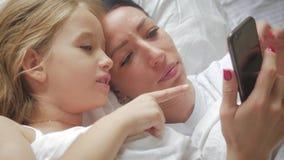 Νέα όμορφη μητέρα και η χαριτωμένη κόρη της που παίρνουν selfie με το smartphone και που χαμογελούν στο κρεβάτι στο σπίτι απόθεμα βίντεο