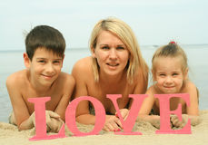 Νέα όμορφη μητέρα με τα παιδιά που βρίσκονται στην παραλία με την αγάπη λέξης Στοκ φωτογραφία με δικαίωμα ελεύθερης χρήσης