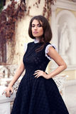 Νέα όμορφη μοντέρνη τοποθέτηση κοριτσιών στο απότομα μαύρο φόρεμα Στοκ Εικόνες