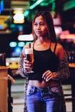 Νέα όμορφη μπύρα κατανάλωσης γυναικών σε έναν φραγμό Στοκ Φωτογραφίες