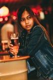 Νέα όμορφη μπύρα κατανάλωσης γυναικών σε έναν φραγμό Στοκ Εικόνες